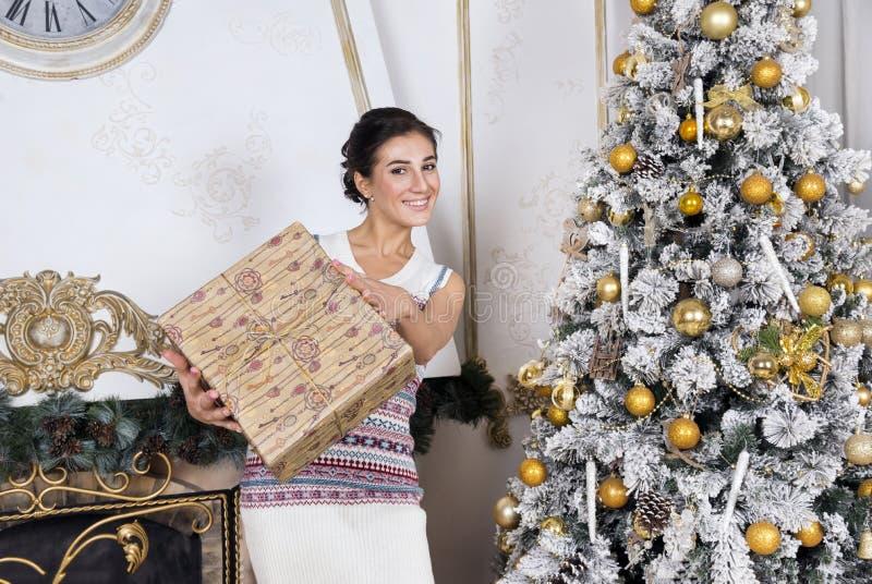 Weißes Mädchen im Strickkleid mit Geschenkbox nahe bei Weihnachtsbaum stockbilder