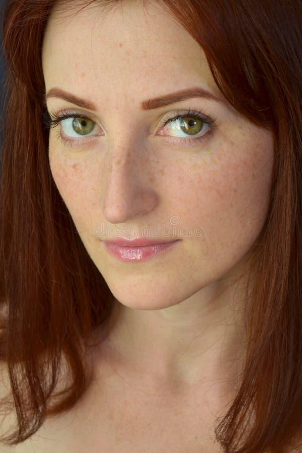 Weißes Mädchen mit dem roten Haar und den grünen Augen mit Sommersprossen mit Wimpererweiterungen auf dem dunklen ernsthaft schau stockfotografie