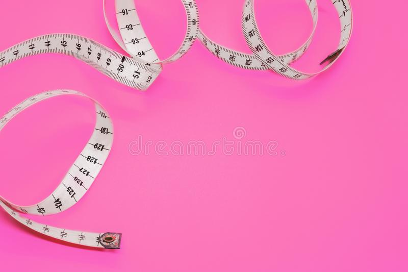 Weißes messendes Band lokalisiert auf rosa Hintergrund Schließen Sie das messende Band des Schneiders auf einem rosa Hintergrund lizenzfreies stockfoto