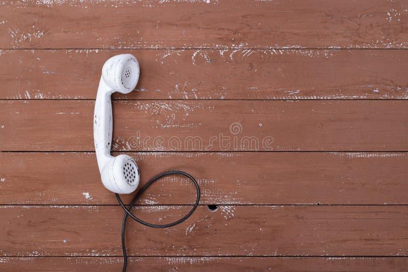 Weißes mit der Hand festgemachtes Weinlesetelefon der Draufsicht auf einem braunen Holz gemasert lizenzfreies stockbild
