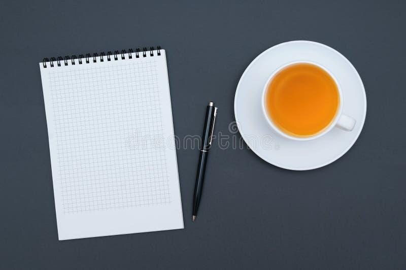 Weißes Notizbuch in einem Käfig ein blauer Stift und eine Schale grüner Tee auf einem dunkelgrauen Hintergrund stockfotografie