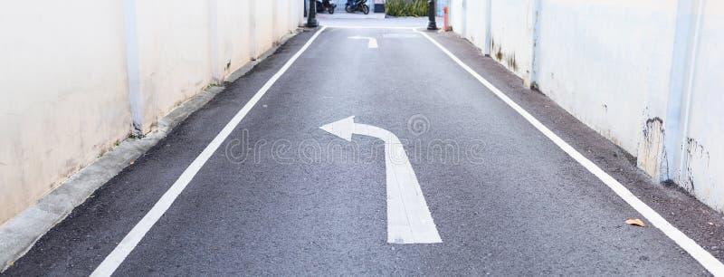 Weißes PfeilVerkehrszeichen zeigt Nebenstraße an, um zur Hauptstraße und zu den weißen Fußwegenlinien auf der Asphaltlandstraße h stockfotografie