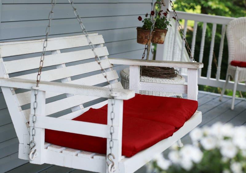 Weißes Portalschwingen mit roten Kissen stockfoto