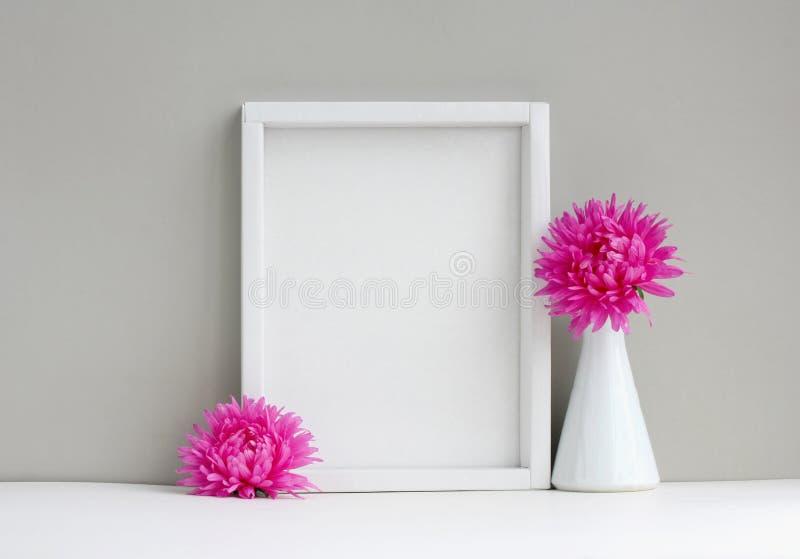 Weißes Rahmenmodell, leerer Plan, Vase mit rosa Aster stockbild