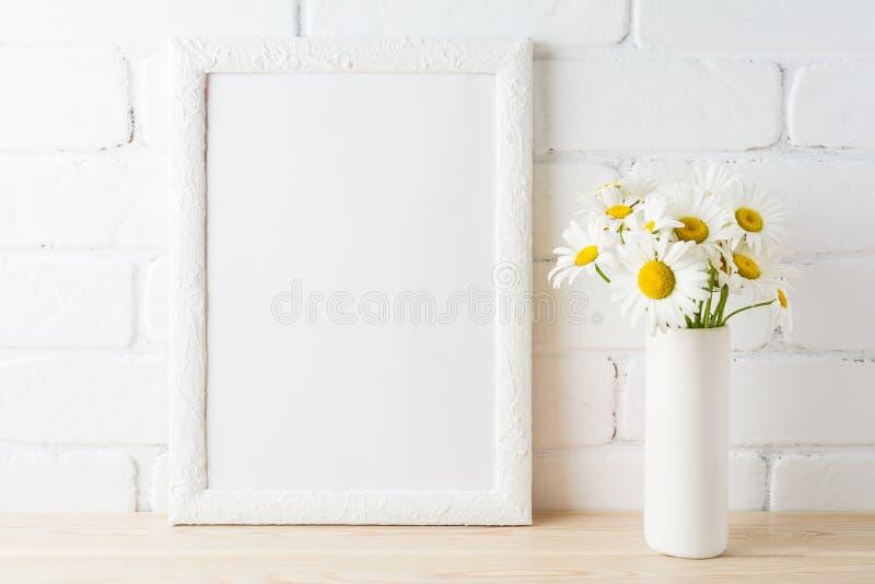Weißes Rahmenmodell mit Gänseblümchenblume nahe malte Backsteinmauer stockbilder