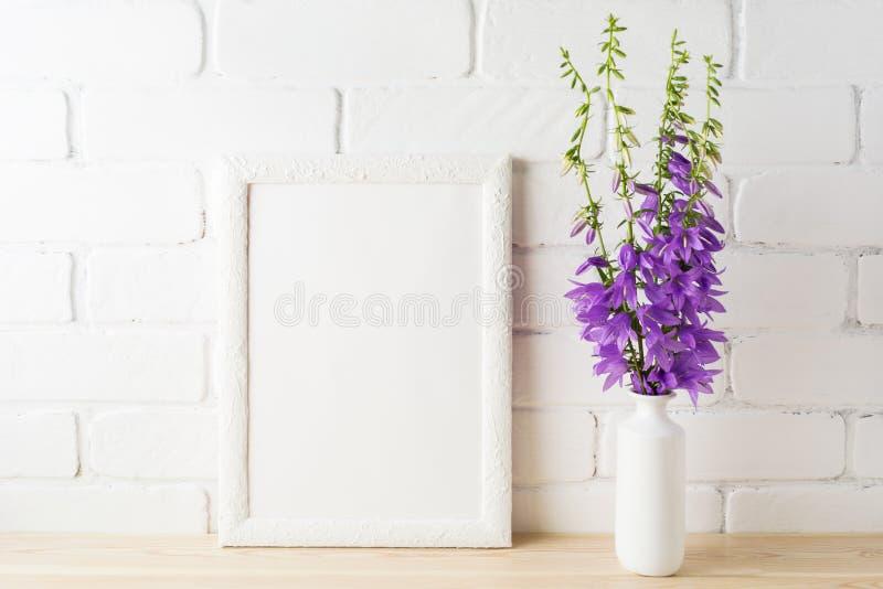 Weißes Rahmenmodell mit purpurrotem Glockenblumeblumenstrauß nahe Backsteinmauer lizenzfreie stockfotografie