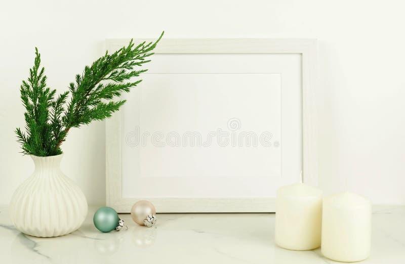 Weißes Rahmenmodell mit Thuja brances im weißen Vase stockbild