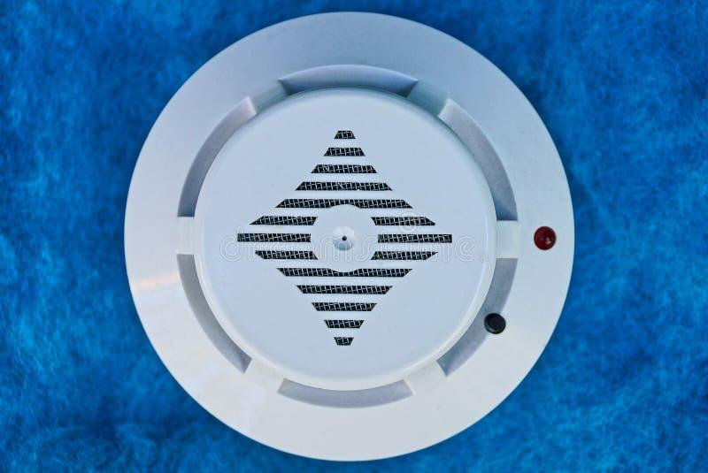 Weißes rundes Plastikfeuermeldergerät auf der blauen Wand lizenzfreies stockbild