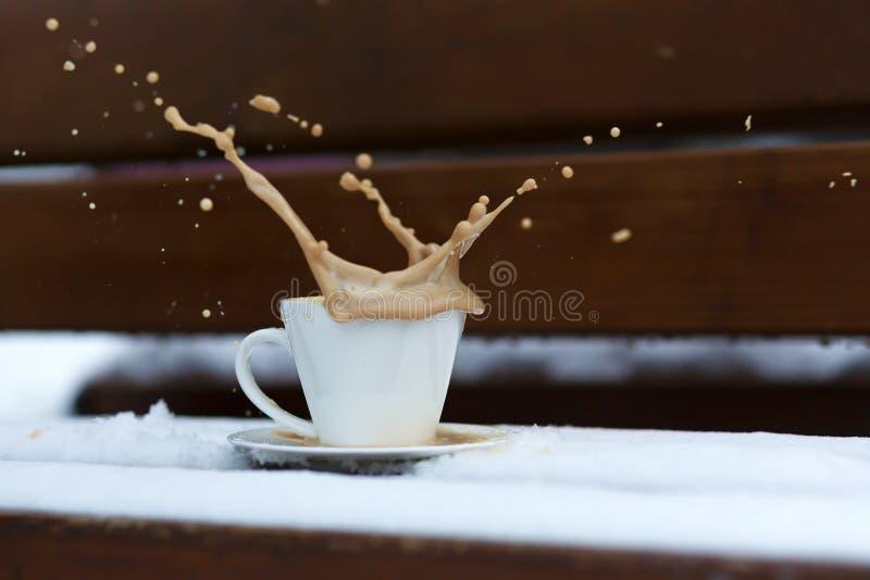 Weißes Schalenspritzen mit heißem Kaffee, der im Schnee auf einer Holzbank an einem kalten Wintertag steht lizenzfreie stockbilder