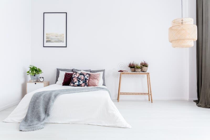 Weißes Schlafzimmer mit Blumenkissen stockfotografie