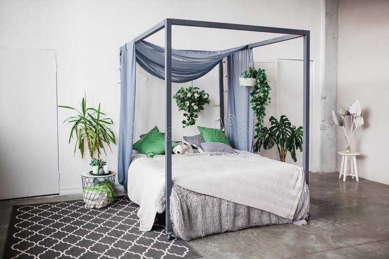 Weißes Schlafzimmer mit einfachen Dekoreinzelteilen im Strand redete Hauptwohnung mit dem Grün, Zimmerpflanzen an lizenzfreie stockfotografie