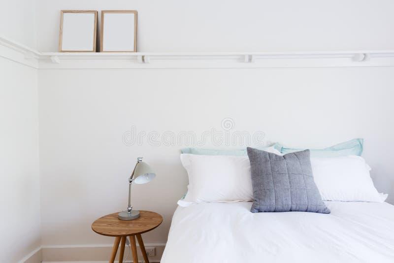 Weißes Schlafzimmer mit einfachen Dekoreinzelteilen im Strand redete nach Hause an lizenzfreie stockfotos