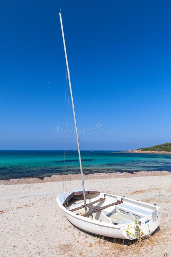 Weißes Segelboot legt auf den Strand, Korsika lizenzfreie stockfotografie