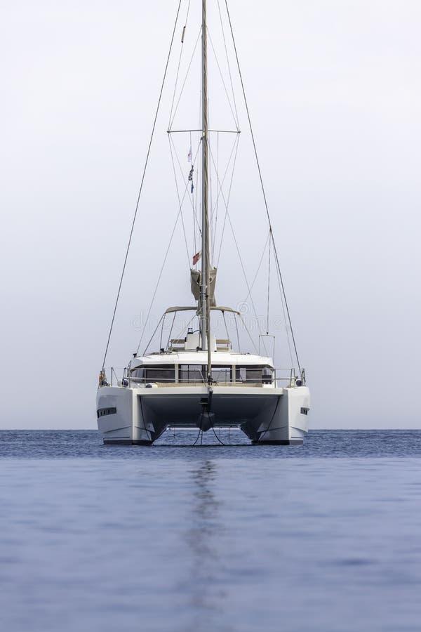 weißes Segelbootkatamaran auf Ozean nahe Strand lizenzfreies stockfoto