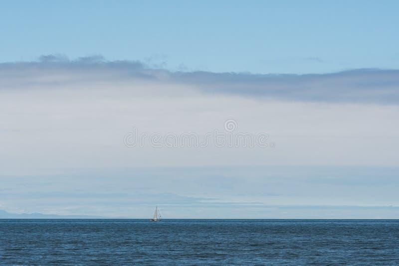 Weißes Segelbootkreuzen ein Muschel Salish-Meer, San Juan Islands, blauer Himmel mit weißen Wolken im Hintergrund stockbilder