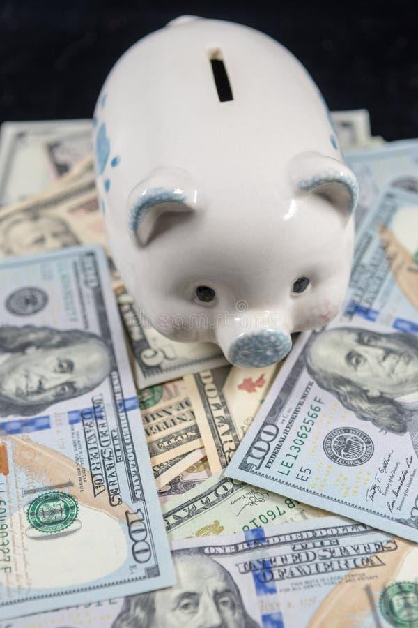 Weißes Sparschwein auf einem Stapel von Währung Vereinigter Staaten gegen einen schwarzen Hintergrund stockfotos