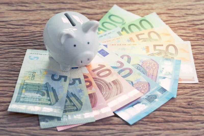 Weißes Sparschwein auf Stapel von Eurobanknoten auf Holztisch, fina stockbild