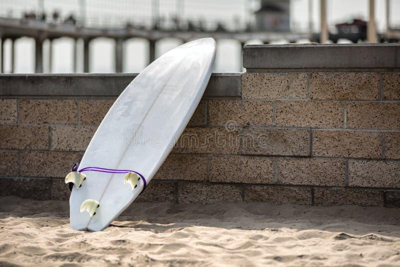 Weißes Surfbrett, das auf der Steinwand sich lehnt stockfotografie
