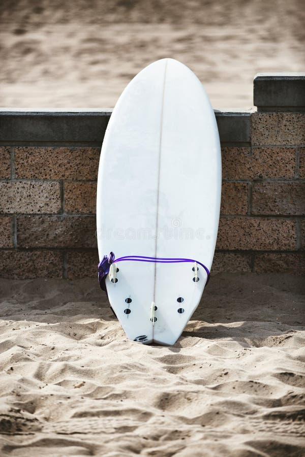 Weißes Surfbrett, das auf der Steinwand sich lehnt lizenzfreies stockbild