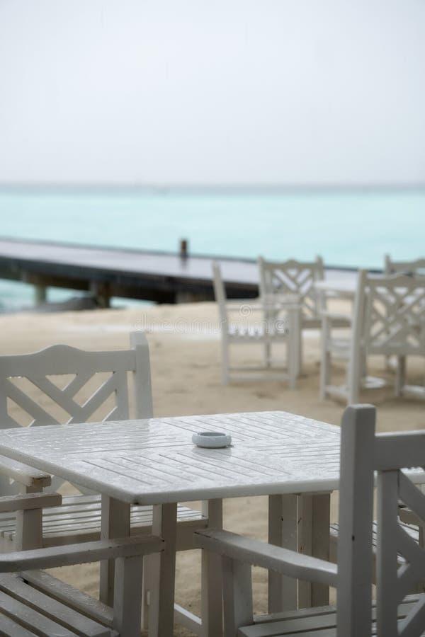 Weißes Tabellenrestaurant auf dem Strand Die Regenzeit hat angefangen lizenzfreie stockfotografie