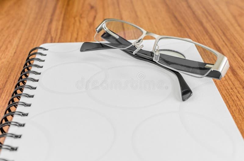 Weißes Tagebuch und schwarze Gläser stockfoto