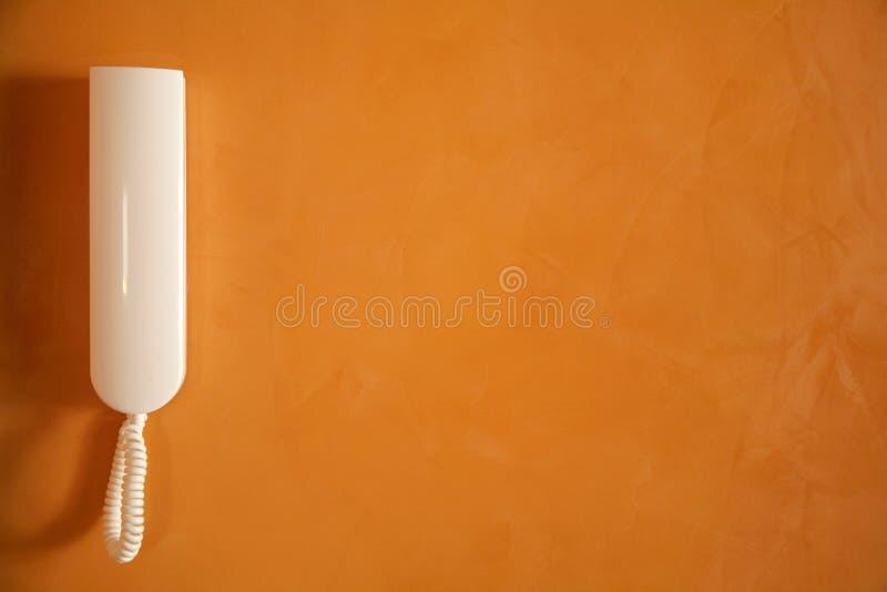 Weißes Telefon auf orange Wand stockfoto