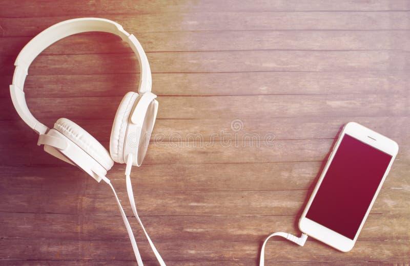 Weißes Telefon und Kopfhörer auf Holztisch Warmes gelbes getontes Foto lizenzfreies stockfoto