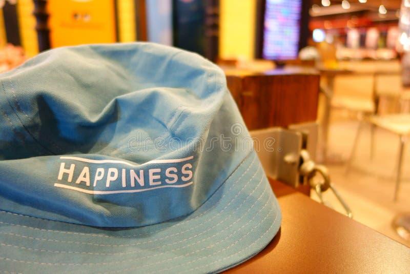 Weißes Text-Glück im blauen Schnallen-Hut auf warmem orange Backgroun lizenzfreies stockfoto