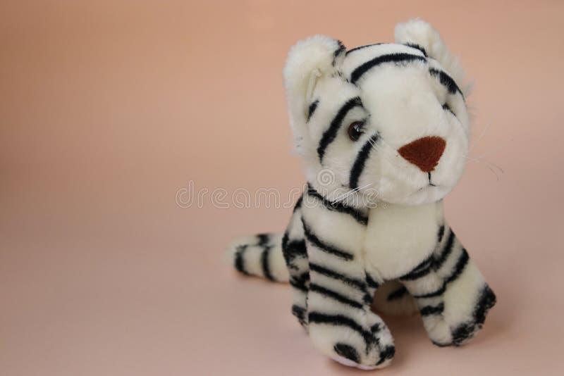 Weißes Tigerjunges des Spielzeugs auf Pfirsichhintergrund mit Reflexion des Schattens lizenzfreie stockfotografie