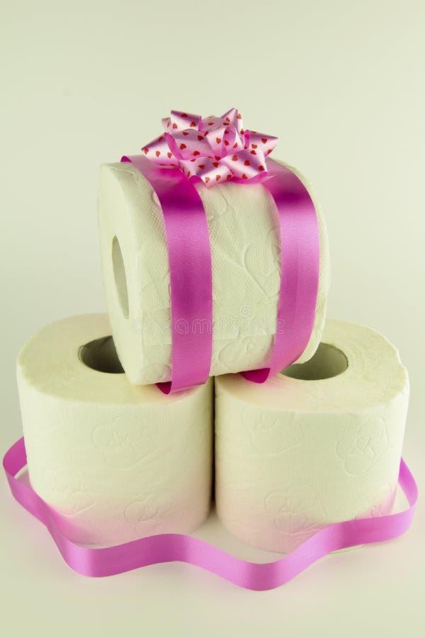 Weißes Toilettenpapier mit einer Beschaffenheit gebunden mit einem rosa Geschenkband w lizenzfreies stockbild