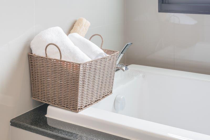 Weißes Tuch im Korb auf Badewanne stockfotos