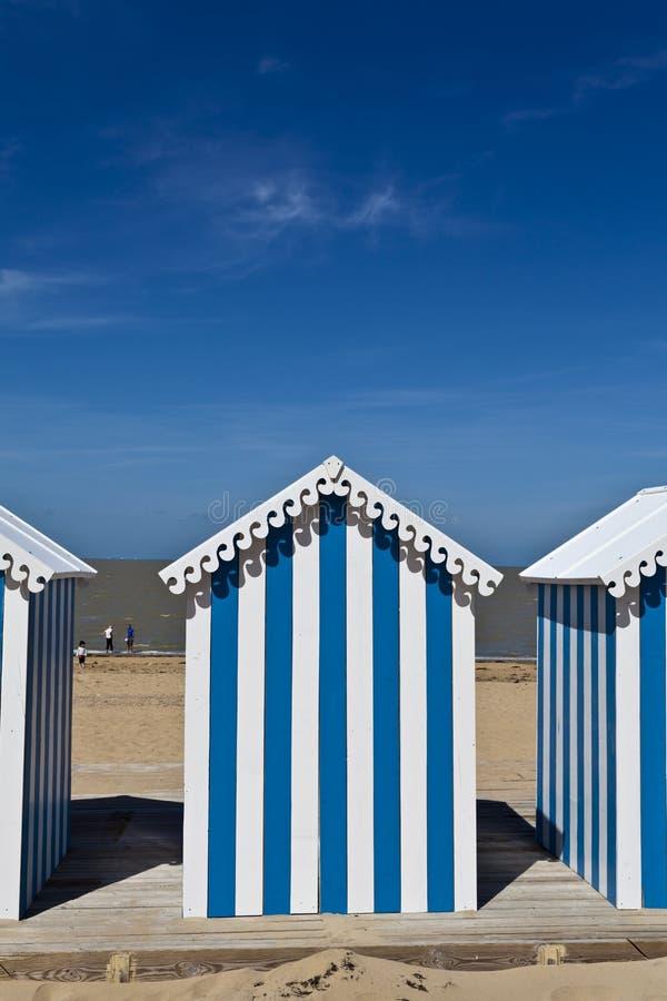 Weißes u. blaues gestreiftes Strandhaus auf einem sonnigen Strand lizenzfreie stockbilder