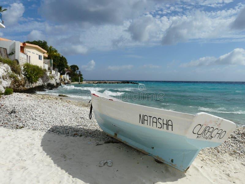 Weißes und blaues Fischerboot durch das Meer stockfotos