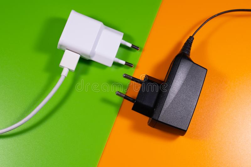 Weißes und schwarzes allgemeinhinladegerät auf orange und grünem Hintergrund stockbilder