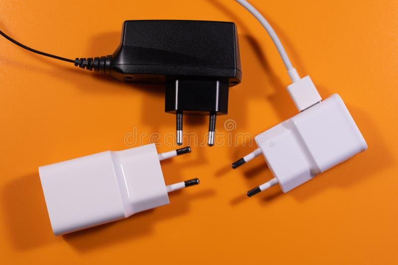Weißes und schwarzes allgemeinhinladegerät auf orange Hintergrund lizenzfreies stockbild