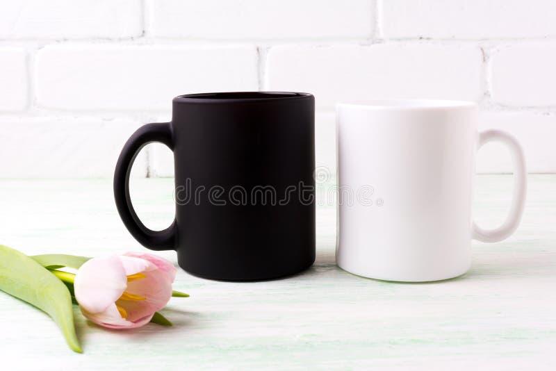 Weißes und schwarzes Bechermodell mit rosa Tulpe lizenzfreies stockbild