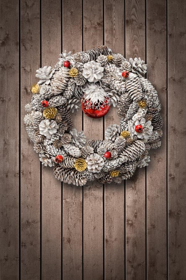 Weißes Weihnachtswreath auf hölzerner Tür stockfotografie