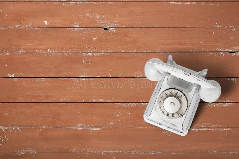 Weißes Weinlesetelefon auf einem braunen Holz gemasert lizenzfreies stockbild