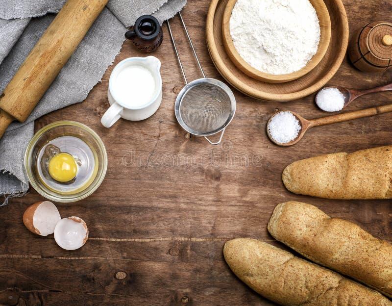 Weißes Weizenmehl in einer hölzernen Schüssel und in gebackenen Stangenbroten stockbild
