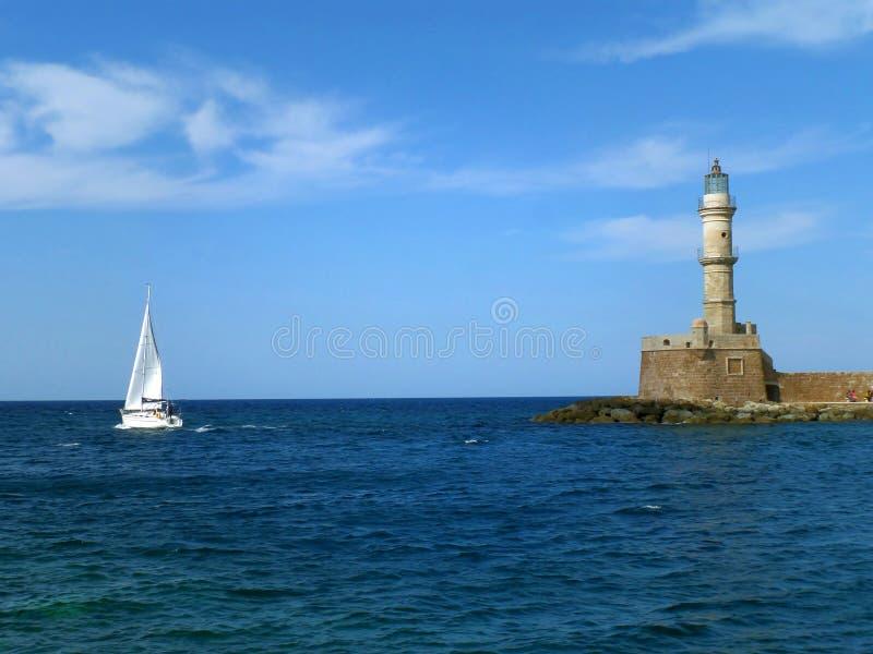 Weißes Yacht-Segeln nahe dem historischen Leuchtturm am alten venetianischen Hafen in Chania, Kreta-Insel von Griechenland lizenzfreie stockbilder