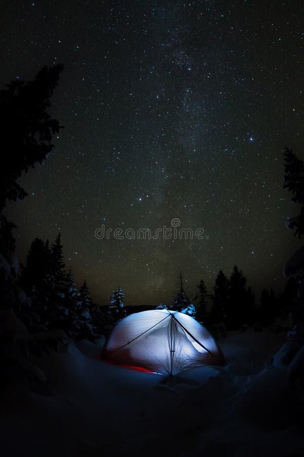 Weißes Zelt unter dem sternenklaren Himmel und die Milchstraße in den Bäumen in den Winterbergen nachts stockfotos
