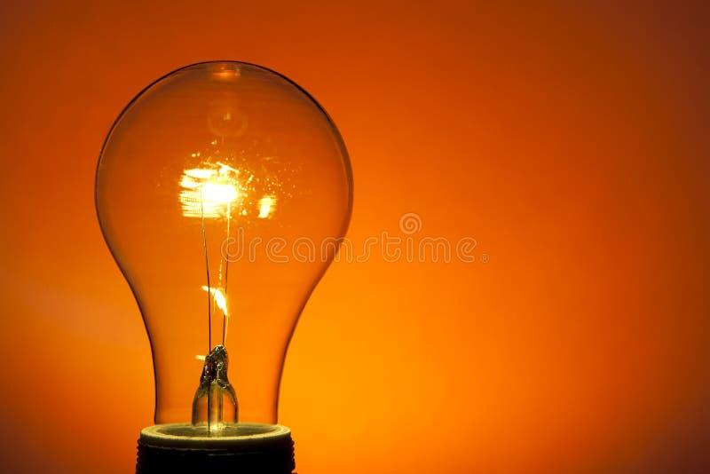 Weißglühende Glühlampe auf Orange lizenzfreie stockfotografie