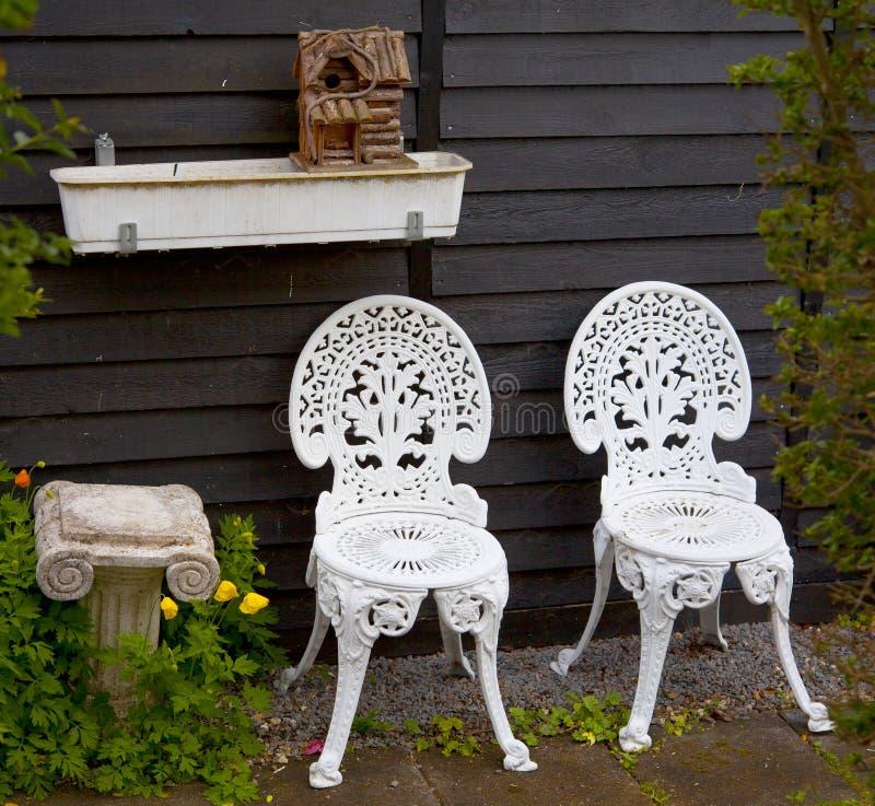 Weißmetall-Garten-Stühle nahe bei kleiner Spalte und Vogelhaus stockfoto