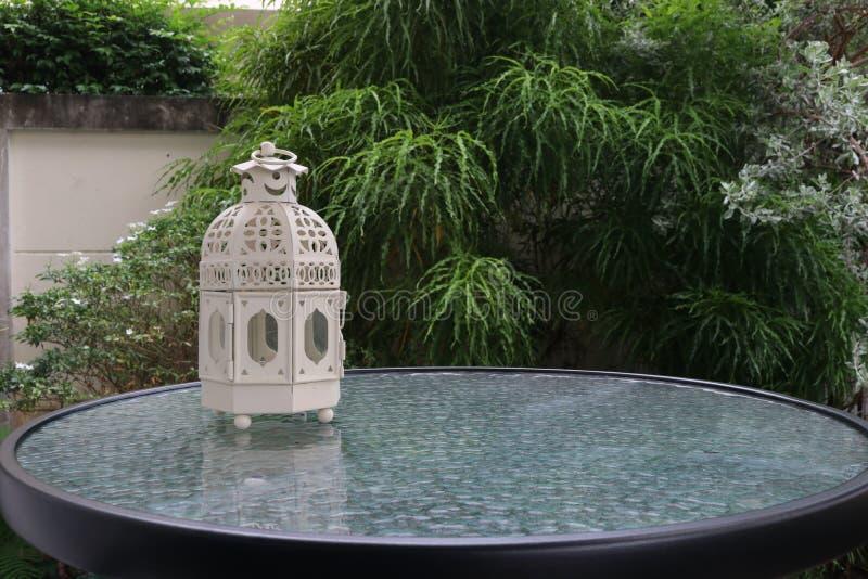 Weißmetall lattern im Retro- Design auf Spiegeltabelle im Garten lizenzfreie stockfotografie