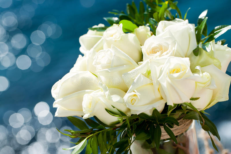Weißrosenblumenstrauß gegen blauen Hintergrund. stockfoto