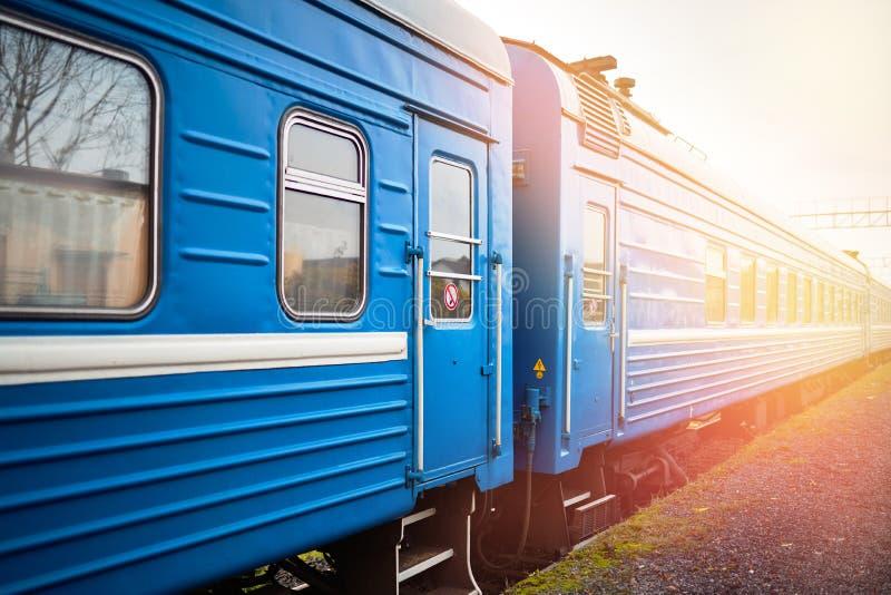Weißrussischer Personenzug wartet auf Passagiere am Bahnhof mit orangefarbenen Flecken von Abendsonne stockbilder