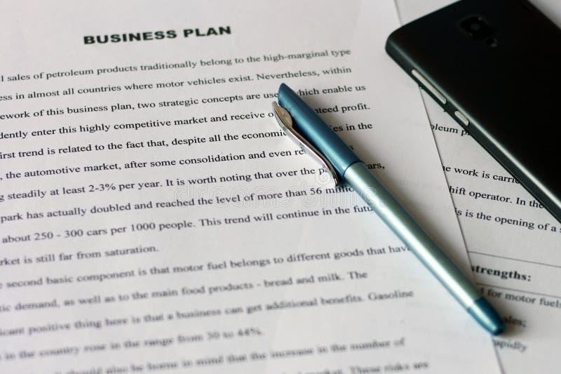 Weiße Blätter Papier mit Drucktext auf dem Tisch mit einem blauen Stift und einem schwarzen Smartphone Revidierung von Finanzberi lizenzfreie stockfotos
