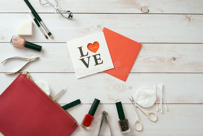 Weiße Karte mit einem Muster in Form von Herzen, Maniküresatz und Nagellack auf hölzernem Hintergrund Valentinsgruß `s Tag flatla stockbild