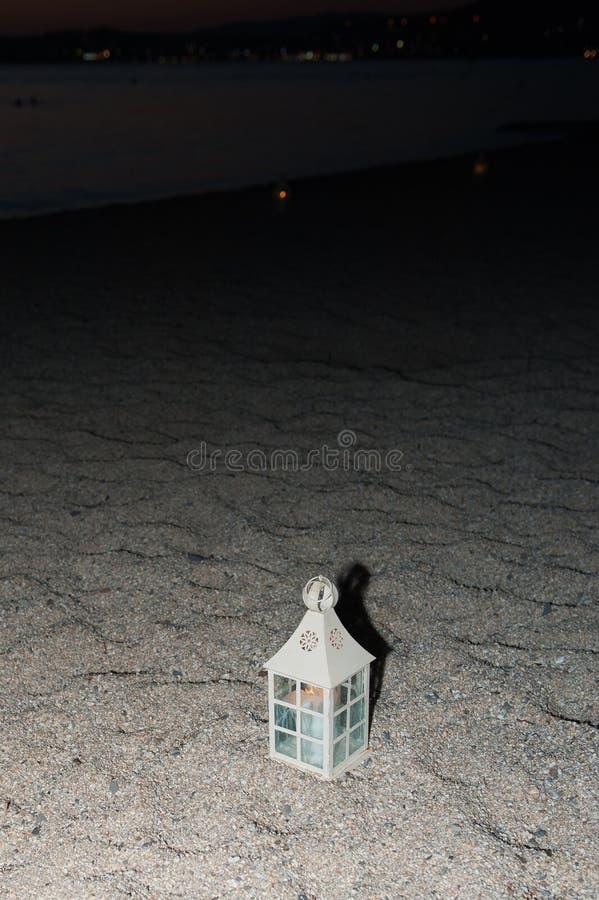 Weiße Laterne auf der Küste nachts Stellung auf dem Sand stockbilder