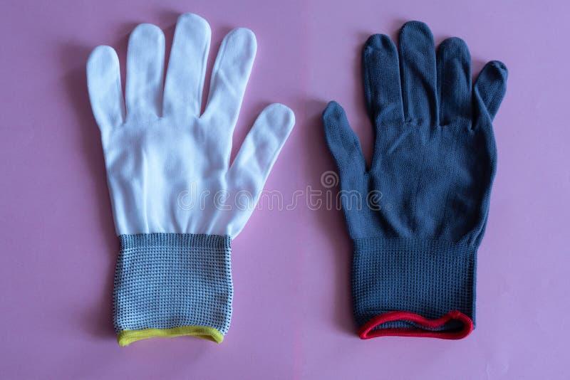 Weiße und schwarze Arbeitshandschuhe auf rosa Hintergrund Overall und Uniformen Handschutz lizenzfreie stockbilder